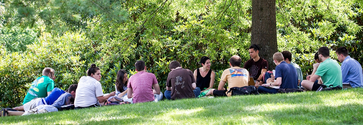 Class sitting in a circle outside under the shade of trees